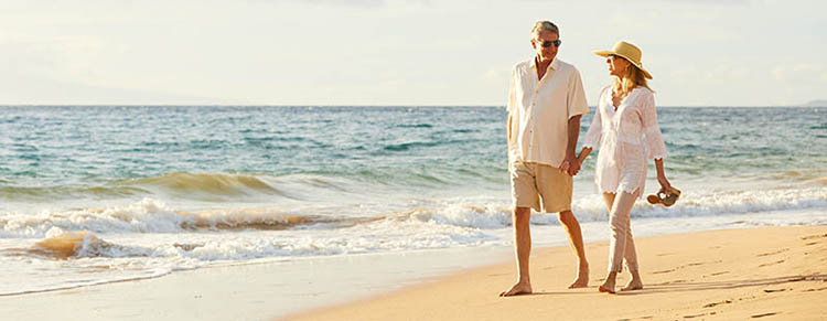 Retired couple walking on beach